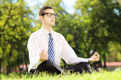 Young businessperson meditating seated on a green grass in a par Stock Images