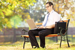 Young businessperson sitting on a bench and working on a laptop Stock Images