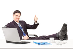 Young businessperson sitting on a chair with his legs up and giv Royalty Free Stock Photography