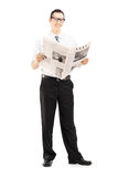 Young businessperson standing and reading a newspaper Royalty Free Stock Images