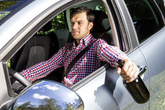 Young businesssman drinking alcohol while driving Royalty Free Stock Images