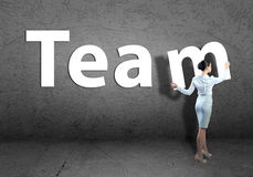 Young businesswoman adds team word Stock Photo