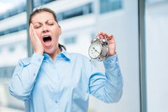 Young businesswoman with an alarm clock yawning Royalty Free Stock Images