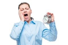 Young businesswoman with an alarm clock yawning on a white Royalty Free Stock Photo