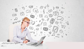 Young businesswoman with all kind of hand-drawn media icons in b Royalty Free Stock Image