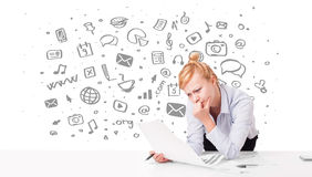 Young businesswoman with all kind of hand-drawn media icons in b Royalty Free Stock Photography