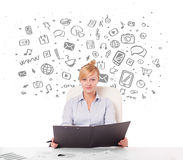 Young businesswoman with all kind of hand-drawn media icons in b Royalty Free Stock Images