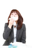 Young businesswoman with an allergy sneezing into tissue Royalty Free Stock Photo