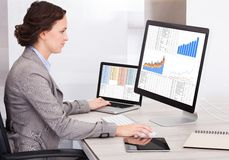 Young businesswoman analyzing graph on computer Stock Photos
