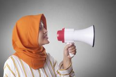 Young Businesswoman Angry, Screaming Using Megaphone. Young Asian businesswoman wearing suit and hijab screaming on megaphone with an angry expression. Close up royalty free stock photos