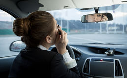 Young businesswoman applying mascara in car Stock Photography