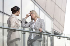 Young businesswoman arguing with female colleague at office railing Stock Image