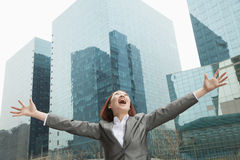 Young businesswoman with arms outstretched and head back among skyscrapers, Beijing Stock Photography