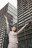 Young businesswoman with arms outstretched among skyscrapers, Beijing Royalty Free Stock Image