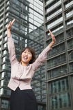 Young businesswoman with arms outstretched among skyscrapers, Beijing Royalty Free Stock Images