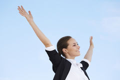 Young businesswoman. With arms up against blue sky Stock Photos