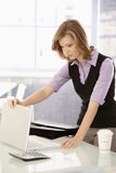 Young businesswoman arriving to office. In the morning, opening her laptop, coffee on table Stock Image