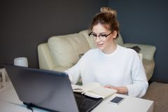 Young businesswoman. Beautiful girl with glasses working at home with laptop Stock Photography