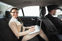 Young businesswoman being chauffeured while working. In the car Royalty Free Stock Photography