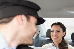 Young businesswoman being chauffeured while working Royalty Free Stock Images