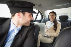 Young businesswoman being chauffeured while working. In the car stock images