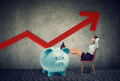 Young successful businesswoman with big piggy bank relaxing sitting on chair royalty free stock photography