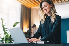 Young businesswoman in black blouse is standing indoor, working on computer. Girl freelancer, entrepreneur works at home. Young smiling businesswoman in black Stock Images