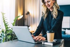 Young businesswoman in black blouse is standing indoor, working on computer. Girl freelancer, entrepreneur works at home. Young smiling businesswoman in black Royalty Free Stock Photo