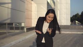 Young businesswoman in black suit screams at the phone on sunny day against the backdrop of office center stock image