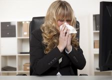 Young businesswoman blowing her nose Royalty Free Stock Photography