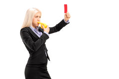 Young businesswoman blowing a whistle and showing a red card. Isolated on white background Royalty Free Stock Photos