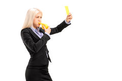 Young businesswoman blowing a whistle and showing a yellow card. Isolated on white background Royalty Free Stock Images
