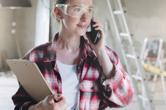 Young businesswoman builder, engineer, architect, designer is standing in repaired room, talking on cell phone Royalty Free Stock Photo