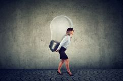 Businesswoman with business idea light bulb on her back Stock Photography