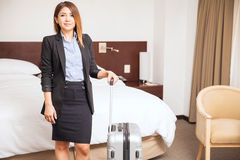 Young businesswoman during a business trip. Pretty young businesswoman holding a suitcase and standing in a hotel room during a business trip Royalty Free Stock Image