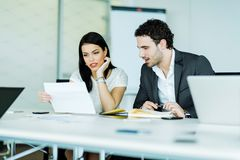 Young businesswoman and a businessman looking at a paper while s Stock Images