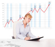 Young businesswoman calculating stock market with rising graph i Royalty Free Stock Images