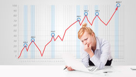 Young businesswoman calculating stock market with rising graph i Stock Photography