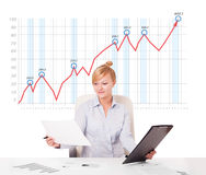 Young businesswoman calculating stock market with rising graph i Royalty Free Stock Photography