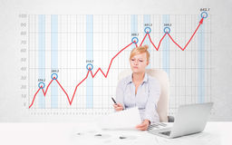 Young businesswoman calculating stock market with rising graph i Royalty Free Stock Image