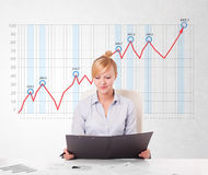 Young businesswoman calculating stock market with rising graph i Royalty Free Stock Photo