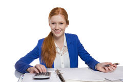 Young businesswoman is  calculating and writing on a paper Stock Images
