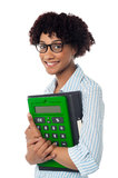 Young businesswoman with calculator and file. Pretty young corporate woman is ready with yearly financial report Royalty Free Stock Photography