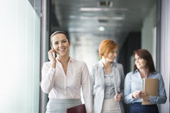 Young businesswoman on call with colleagues in background at office corridor Royalty Free Stock Photography