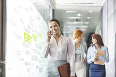 Young businesswoman on call with colleagues in background at office corridor Stock Images