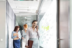 Young businesswoman on call with colleagues in background at office corridor Stock Photo