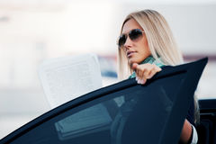 Fashion business woman with financial papers at the car Stock Images