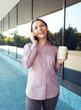 Young businesswoman with cellphone and coffee while standing aga Stock Photography