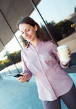 Young businesswoman with cellphone and coffee while standing aga Stock Photo