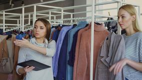 Young businesswoman is checking clothes in her store with tablet in hands. Her employee is coming and asking about stock footage